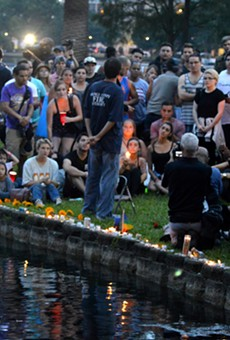 People lay candles at a small vigil for victims of the mass shooting at Pulse nightclub in Orlando.