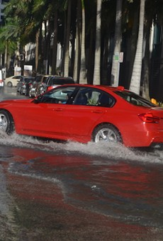 A car drives through flooded streets in Miami