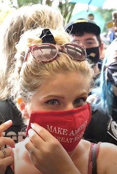 Conservative gun rights activist Kaitlin Bennett puts on her MAGA face covering outside the John C. Hitt library, as per UCF's new COVID-19 policies and UCF PD directives. It took students, staff, and police nearly two hours to get her to comply.