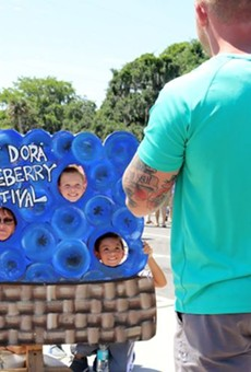 Festival goers at the 2018 Mount Dora Blueberry Festival take pictures in the blueberry sign.