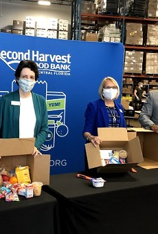 Second Harvest Food Bank board members unbox food distributed from Mercy Kitchen, courtesy of Second Harvest Food Bank of Central Florida