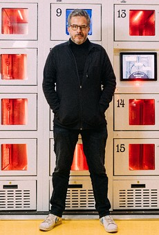 Founder Stratis Morfogen in front of a wall of heated lockers at Brooklyn Dumpling Shop.