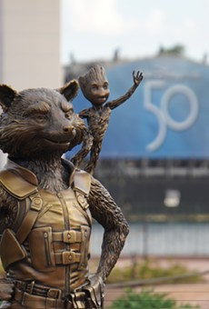 Rocket and Groot Fab 50 statue at Epcot with the 50th-anniversary logo seen on a Harmonious barge LED screen behind them.