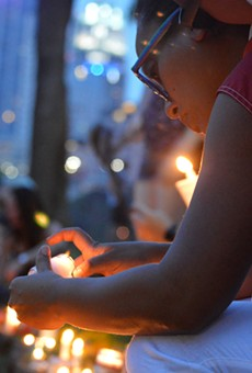 A woman lights a candle at a small vigil for victims of the mass shooting at Pulse nightclub in Orlando.