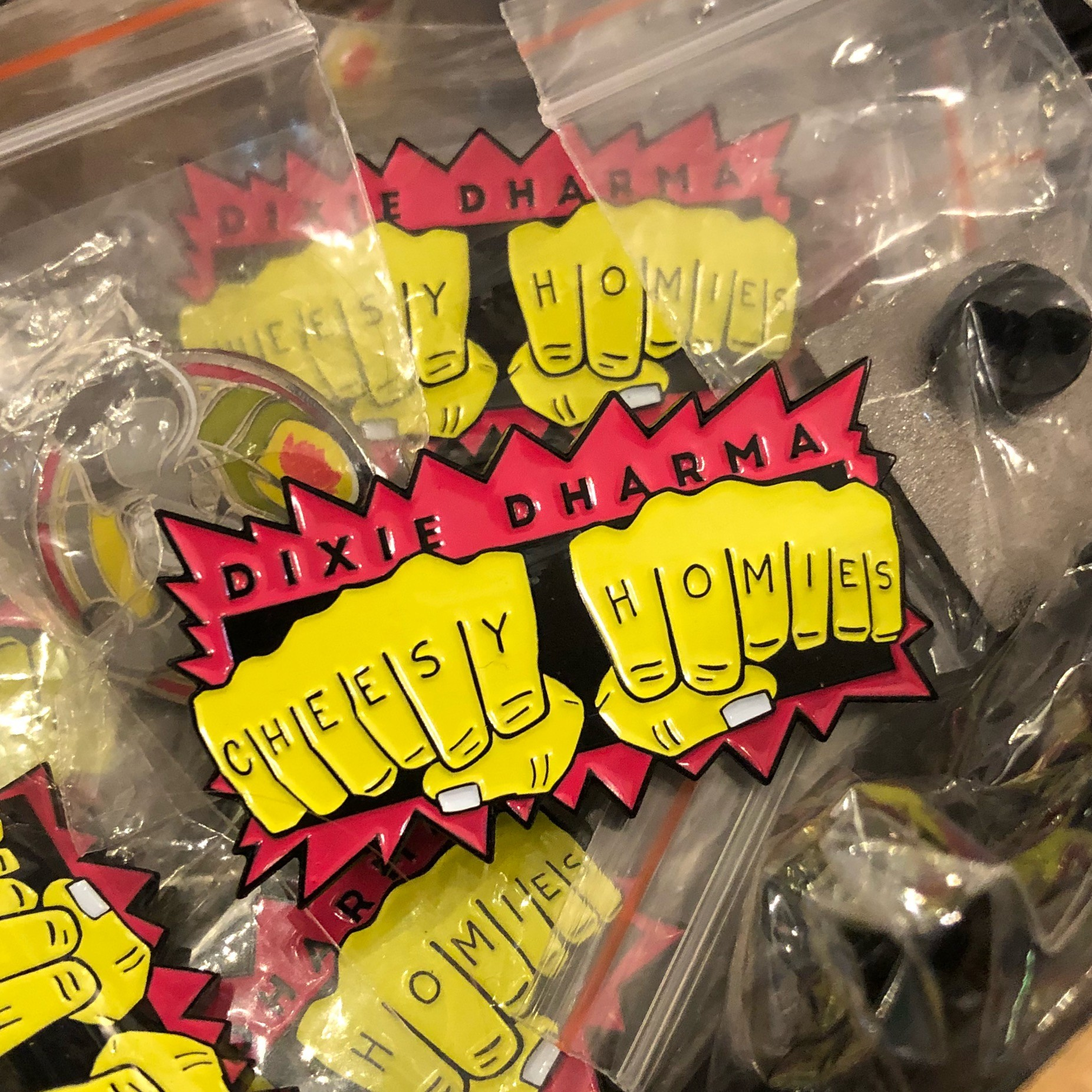 "Dixie Dharma ""Cheesy Homies Knuckle Tat"" enamel pin - PHOTO BY JESSICA BRYCE YOUNG"