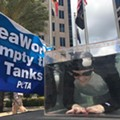 PETA protests SeaWorld in downtown Orlando by putting orca-woman in tiny water tank