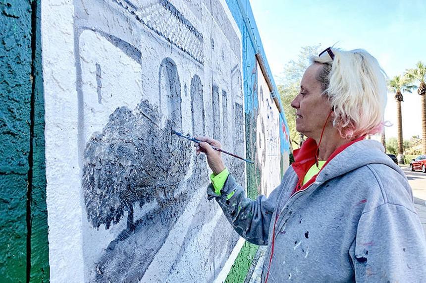 Lucretia Torva works on a mural in the FQ Story neighborhood. - STEVE DREISESZUN