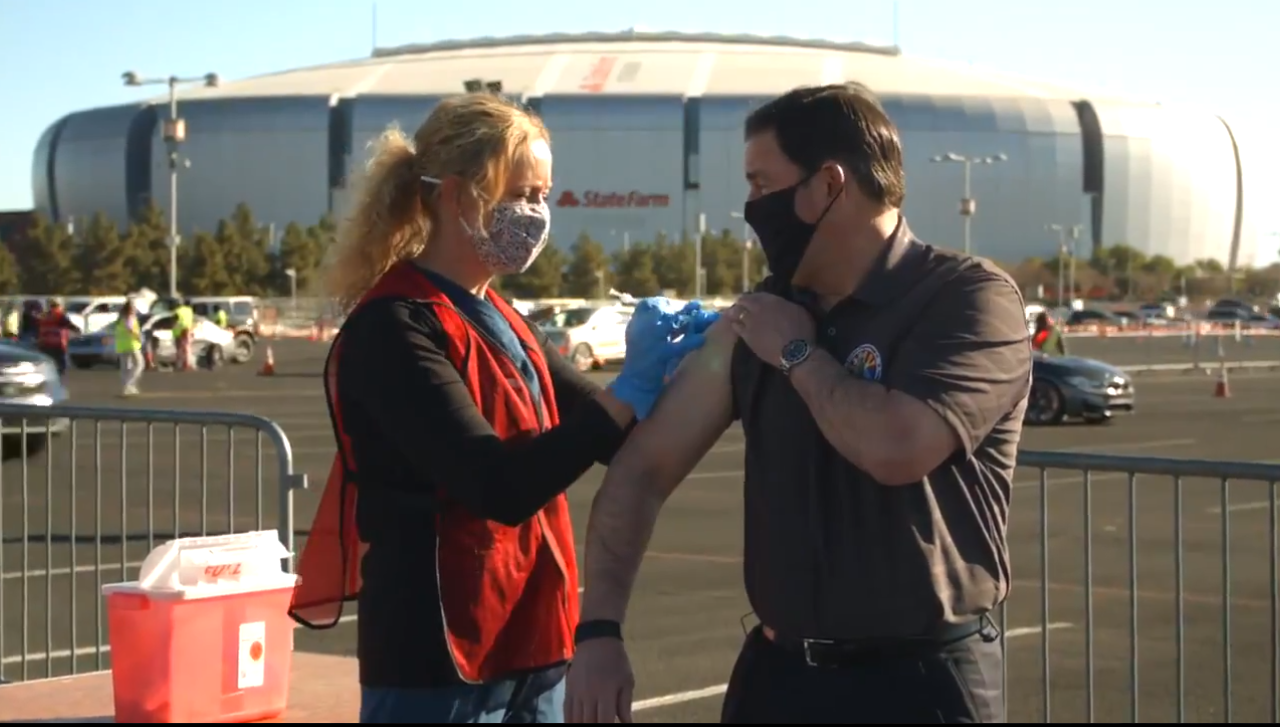 Governor Doug Ducey gets a dose of a COVID-19 vaccine from DHS Director Dr. Cara Christ.