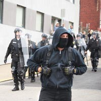 A mask-wearing demonstrator stays a step ahead of the law during the G-20 summit. - CHARLIE DEITCH