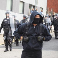 A protester runs in front of police officers during the unpermitted G-20 march in Lawrenceville Sept. 24.