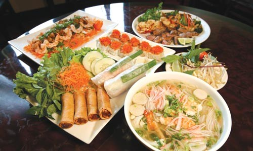 A selection of dishes including fried and fresh spring rolls (front left) and pho hai-san soup (right)