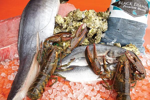 A selection of fresh seafood: ahi tuna, wahoo, oysters, Maine Lobster, bronzini, and Prince Edward Island mussels