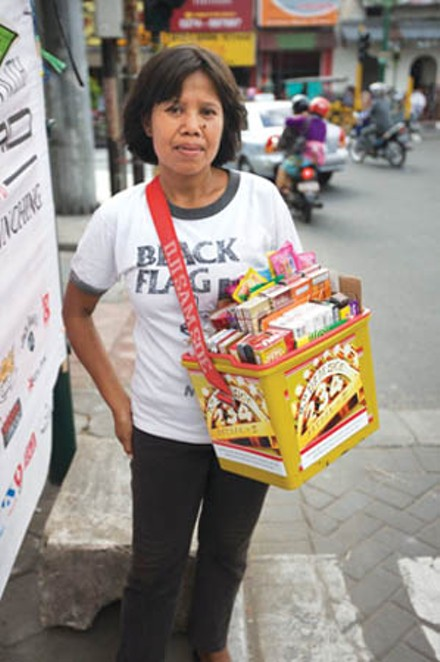 A vendor in Jakarta wearing a Black Flag T-shirt
