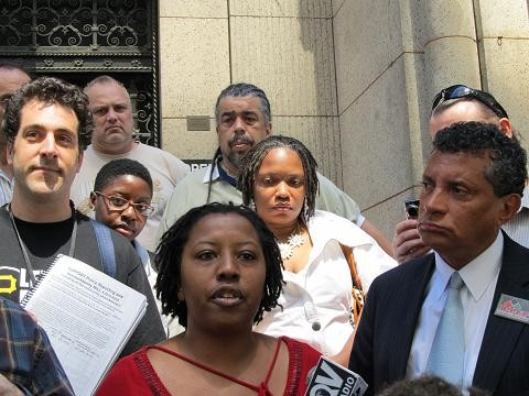 Activist Brandi Fisher (at microphone) urges criminal charges against officers in the Jordan Miles case.