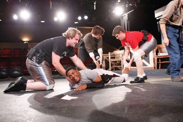 Actors playing police officers stage a fight scene with Corey Talley (center), as Jonny Gammage. - PHOTO BY HEATHER MULL