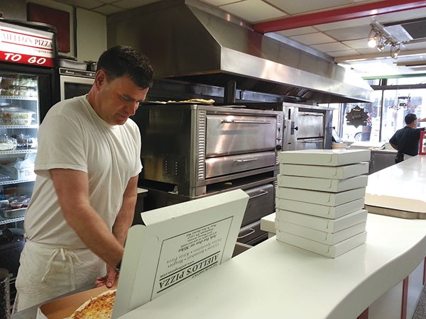Aiello's employee Tim Watts cuts slices of Aiello's pizza for customers mourning the passing of owner Joe Aiello. - PHOTO BY AMYJO BROWN