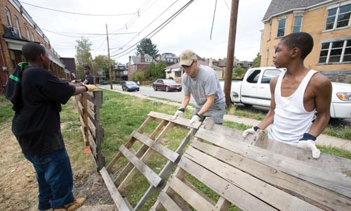 Andrew Butcher of GTECH (center) helps neighborhood kids build a fence. GTECH, a nonprofit, is helping plant biofuel crops in East Liberty.