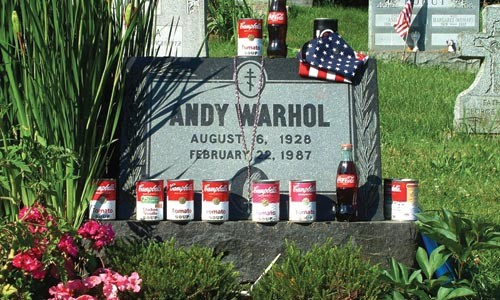 """Andy Warhol's grave, adorned by visitors, in Madelyn Roehrig's """"Figments: Conversations With Andy."""""""