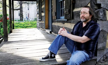 Around my cabin door: Martin Giles sits on the porch of a cabin on the University of Pittsburgh campus; in the background is visible the Stephen Foster Memorial, where his new play Beautiful Dreamers will be staged. - HEATHER MULL
