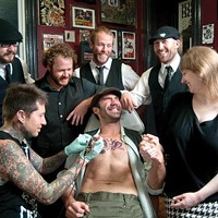 Band members Ben Jaber, Danny Rectenwald, Dan Stocker, Jon Pitcher and Rachel Karras watch as tattoo artist Justun Palencssar works on singer Jimmy Bastard
