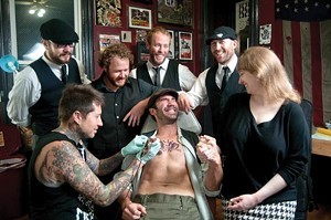 Band members Ben Jaber, Danny Rectenwald, Dan Stocker, Jon Pitcher and Rachel Karras watch as tattoo artist Justun Palencssar works on singer Jimmy Bastard - PHOTO BY CAROLINE MOORE