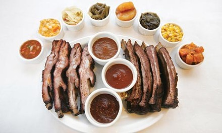 Barbecued pork and beef ribs, with an assortment of side dishes - HEATHER MULL