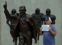 Bernie McCue protests next to the Joe Paterno statue in Happy Valley