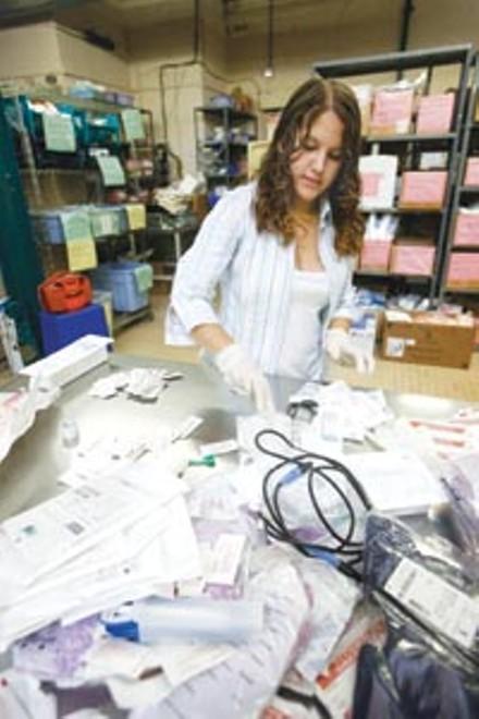 Carnegie Mellon work-study student Angelina Gonzalez processes medical surplus for shipment overseas. - HEATHER MULL