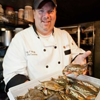 The Wooden Nickel Chef de cuisine Craig Wolf shows off the live soft-shell crabs in the walk-in cooler Photo by Heather Mull