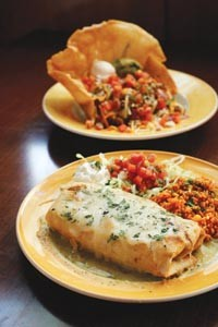Chicken chimichanga with rice, and taco salad (rear) - HEATHER MULL