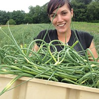 Dana Waelde carrying garlic scapes at Blackberry Meadows