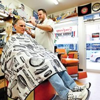 Dennis Scullion trims the hair of customer Jack Linn in the barbershop Scullion's grandfather started in 1931.