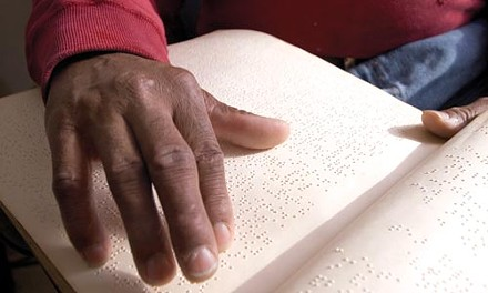 Dorsey reads his Braille Bible.