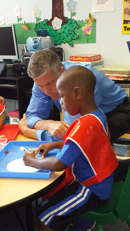 Education Secretary Arne Duncan works with a student at Hug Me Tight