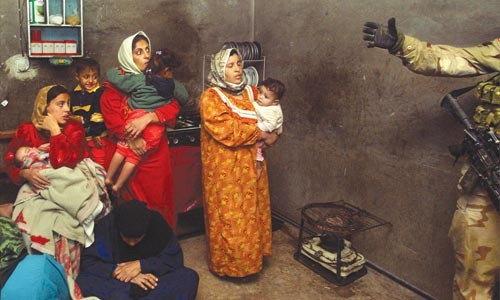 "Facing Conflict: Chris Hondros' ""Iraqi Family Looking at Soldier"" (2003)"