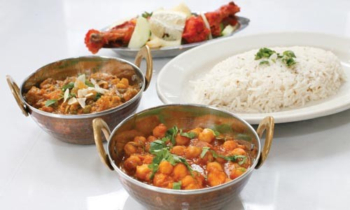 From left, clockwise: Navartan (mixed vegetables), tandoori chicken, spiced rice and aloo cholae (chick peas and potatoes) - HEATHER MULL