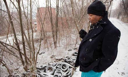 Geneva Jackson checks an illegal dump, strewn with hundreds of tires, near her Hill District home. - BRIAN KALDORF