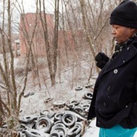 Geneva Jackson checks an illegal dump, strewn with hundreds of tires, near her Hill District home.