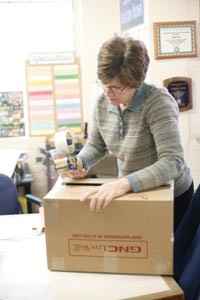 Global Links volunteer Cathy Nalesnik seals a box of re-packed surplus. - HEATHER MULL