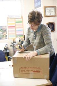 Global Links volunteer Cathy Nalesnik seals a box of re-packed surplus. - HEATHER MULL