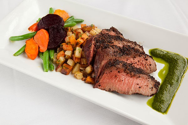 Grilled flat-iron steak with mojo sauce, potato hash and spring vegetable medley