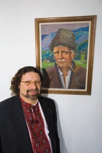 John Righetti, cofounder of the Carpatho-Rusyn Society, stands before a portrait of a Rusyn peasant - HEATHER MULL