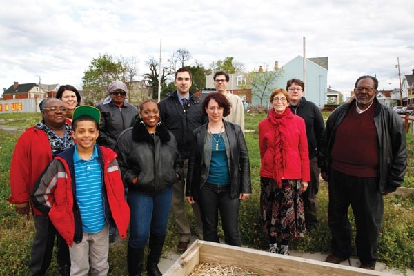 Larimer has hundreds of empty lots — only these lots were repurposed as the Larimer Community Garden. Community volunteers stand before its 40 raised beds.