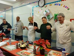 Kevin Hutchison, far right, leads grace before serving meals. Hutchison, now employed as a cook at Light of Life, is a former resident. - PHOTO BY ASHLEY MURRAY