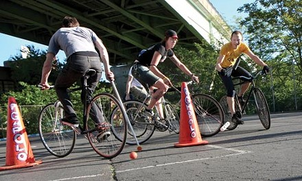 Lindsay Welsh, center, and Jonathan Lomax, right. rush the goal during a recent bike polo match under the Bloomfield Bridge. - JOHN ALTDORFER