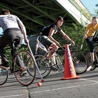 Lindsay Welsh, center, and Jonathan Lomax, right. rush the goal during a recent bike polo match under the Bloomfield Bridge.