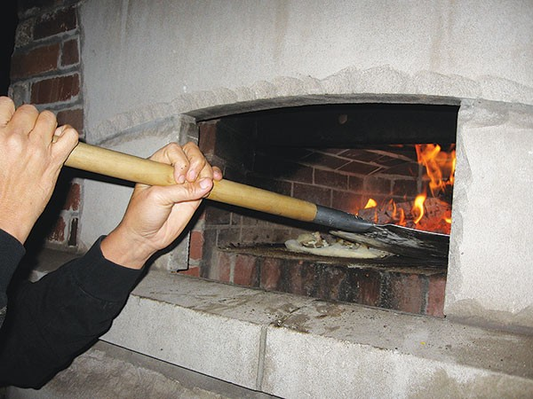 Making pizza in the Braddock community oven