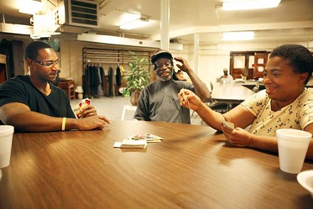 Mark Symms, left, a homeless drop-in center monitor with East End Cooperative Ministries, plays cards on a recent July afternoon with clients Willie Hunter and Jennifer Brooks. More people have been using this and similar services in recent years, while funding has declined. - PHOTO BY HEATHER MULL