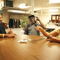 Mark Symms, left, a homeless drop-in center monitor with East End Cooperative Ministries, plays cards on a recent July afternoon with clients Willie Hunter and Jennifer Brooks. More people have been using this and similar services in recent years, while funding has declined.