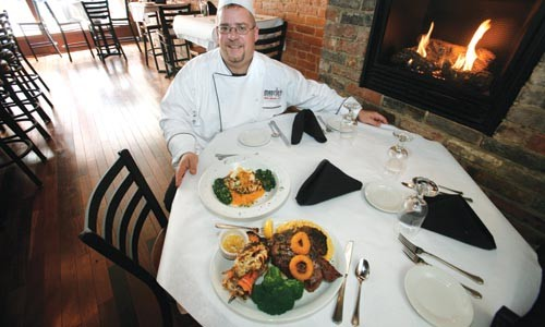 Matt Mantini, with a pair of wood-fired entrees - HEATHER MULL